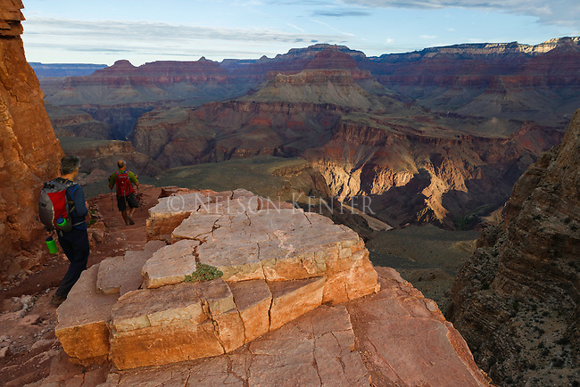 Hikers walking above a spot of sunlight on the canyon walls above the colorado river in the grand canyon