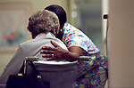 Nurse with caring hand on back of elderly woman in wheelchair at nursing home