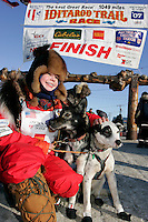 Saturday March 17, 2007  - Nome, Alaska ----   Tekla Monson, daugther of the late Susan Butcher, honorary musher of the 2007 race, poses with her lead dogs Tanis and Ring-a-thing under the Nome burl arch finish line after her and her and her father, David Monson mushed 700 miles from Susan and Dave's old homestead at Manley Hot Springs.