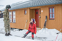 Pilot luitenant Ben Lilley talking to volunteer  Kaisa-Wenche Vivisdatter  while on a mission to transport firewood to a remote Norwegian cabin. The newly built Vouma cabin in Dividalen National Park is part of the Norwegian Trekking Association network. As a goodwill gesture and part of their Arctic training the Royal Navy use helicopters to fly firewood to the remote location. <br /> <br /> <br /> In 2019 the Arctic exercise Clockwork passed 50 years of training in Norway, and now has a permanent base within the Norwegian Air Force base at Bardufoss. <br /> <br /> 845 Naval Air Squadron is a squadron of the Royal Navy's Fleet Air Arm. Part of the Commando Helicopter Force, it is a specialist amphibious unit operating the Leonardo Commando Merlin Mk3 helicopter and provides troop transport and load lifting support to 3 Commando Brigade Royal Marines.<br /> <br /> ©Fredrik Naumann/Felix Features