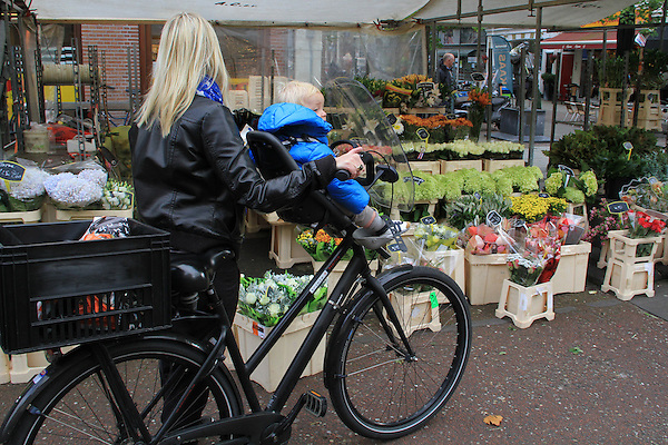 Mother and child on a bike, visiting a flower store, Amsterdam, Netherlands