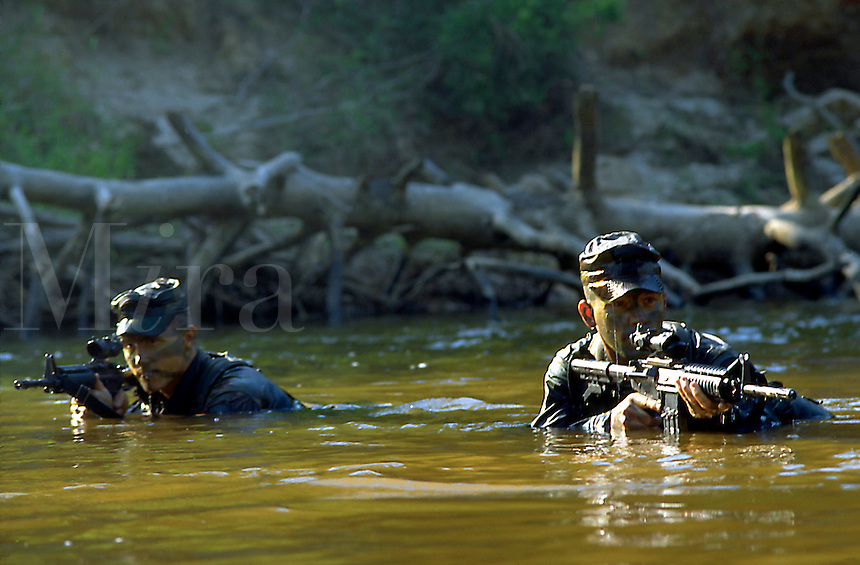 Two Rangers train with rifles in Uchee Creek, at Fort Benning, Georgia.