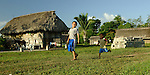 boys run across village lawn in Midway village, southern Belize -- a traditional Mayan village