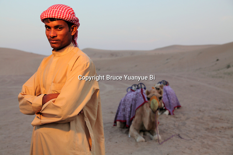 A Bedouin nomad with his camel in Marqub desert. Aub Dhabi. United Arab Emirates.