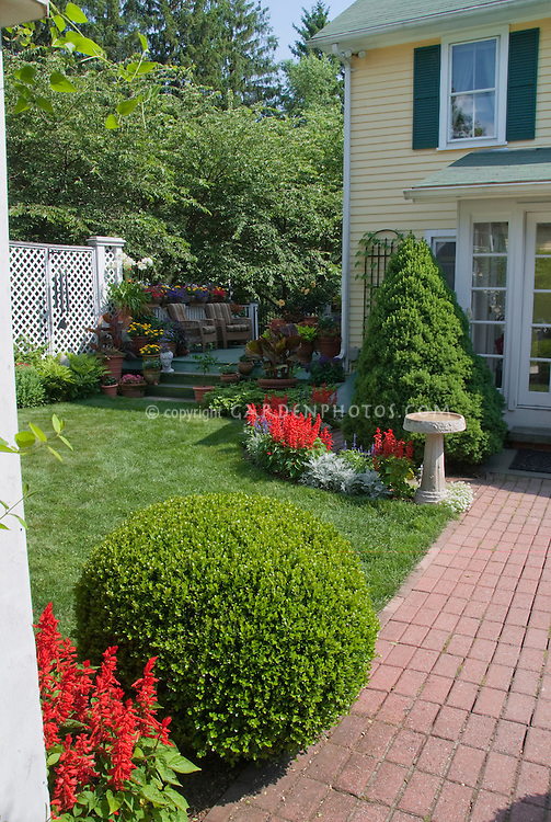 Home landscaping with brick pathway, annual flowers, evergreen shrubs to front of house