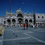 Man in red shirt and woman in black walk toward the Basilica di San Marco.  A pair of piegeons on the patterned pavement;   a cloud-less blue sky, a row of yellow chairs on the left in the piazza and the north end of Doge's Palace seen. Photo of Venice, Italy by Tomoko Yamamoto: original on slide film by Mamiya 6 (Medium Format).<br /> Foto der Markuskirche, Venedig, Italien. Ein Mann im roten Hemd und eine Frau im schwarzen Hemd spazieren auf dem Markusplatz, dem Piazza San Marco.