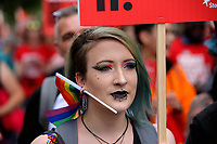A woman with a rainbow flag pierced into her ear joins thousands of people in this year's Pride Parade in the centre of Cardiff, Wales, UK. Sayurday 26 August 2017