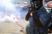 An officer watching to explosion of tens of meters long firecrackers while protecting his face from smoke in the city.....End of year 2010 celebrations on the streets of Paramaribo. Suriname is one of biggest consumer in South America that using firecrackers, fireworks ( also locally known as pagara ) for celebrations, especially for end of every years and also beginning of every new Chinese Years.