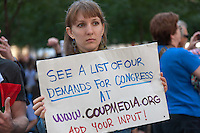 A woman holds a sign in Zuccotti Park indicating the website where a list is demands for Congress can be found during the Occupy Wall Street demonstration in New York City, New York.