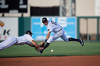 Lakeland Flying Tigers second baseman A.J. Simcox (12) and shortstop Cole Peterson attempt to field a ground ball during a Florida State League game against the Palm Beach Cardinals on April 17, 2019 at Publix Field at Joker Marchant Stadium in Lakeland, Florida.  Lakeland defeated Palm Beach 1-0.  (Mike Janes/Four Seam Images)