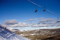 Skiers and snowboarders ride a chairlift at Showdown Ski Area on King's Hill in the Little Belt Mountains near Neihart, Montana, USA.