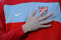 A USA player places his hand over his heart ad US Soccer emblem during the national anthems