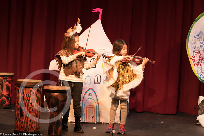 Two female students playing violins on stage during performance at public elementary school for the gifted