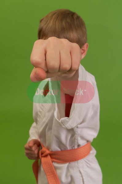 young boy dressed in karate outfit posing with fist in front of face