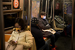 Subway riders wear face masks in New York, U.S., on Thursday, March 19, 2020. New York state Governor Andrew Cuomo on Thursday ordered businesses to keep 75% of their workforce home as the number of coronavirus cases rises rapidly. Photograph by Michael Nagle/Redux