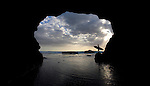 A surfer stands inside a cave with his surfboard, at sunset, at Muriwai Beach. Muriwai is located on the west coast of the North Island of New Zealand, near West Auckland.