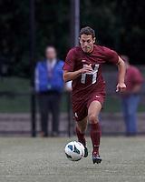 Harvard University defender Ross Friedman (4) brings the ball forward. Boston College (white) defeated Harvard University (crimson), 3-2, at Newton Campus Field, on October 22, 2013.