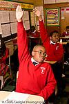K-8 Parochial School Bronx New York Grade 4 boys raising hands for attention in class vertical
