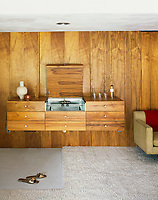 A vintage home bar has been incorporated into a wall-mounted storage unit in the living room