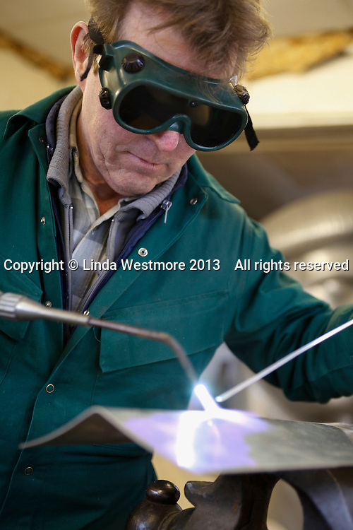 Welding with an oxy acetylene torch.  Adrian Rice, panel beater, working on the resoration of a Jaguar XK 120.  First he builds a wooden formwork then makes new aluminium panels to fit it.  Once the panels are fixed in position, the wooden formwork is removed.