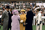 Queen Elizabeth,  Queen Mother, Princess Ann and courtiers and  at the Derby Day horse racing Epsom Downs. Lord Porchester the Earl Carnarvon half back view in black tail coat.