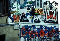 Milano, 1990.Veduta esterna della casa occupata di via Vigevano. I muri sono coperti di graffiti e scritte politiche..Foto Livio Senigalliesi