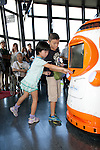 """August 01 2012, Tokyo, Japan - Kids touch the new robot guide """"Tawabo"""" at Tokyo Tower. Tokyo Tower implemented the new robot guide which name is """"Tawabo"""", the first indoor robot guide in Japan. It can speak Japanese, English, Chinese and Korean, it weights 200kg and it is 160cm tall."""
