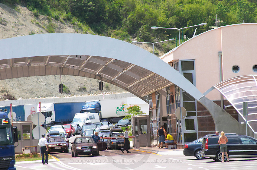 The border crossing between Croatia and Montenegro with a futuristic border control building and customs checkpoint with wing-like construction. Long queues lines of cars and trucks waiting to pass the control. Montenegro, Balkan, Europe.