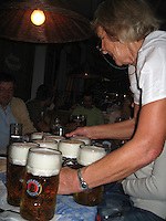 Woman serves huge steins of beer at Oktoberfest - Munich, Germany