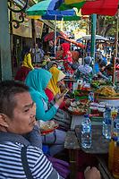 Yogyakarta, Java, Indonesia.  Women Checking their Cell Phones at a Sidewalk Breakfast Stand, Malioboro Street.