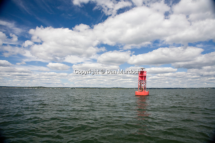 Red buoy on still water under a puffy cloudy blue sky