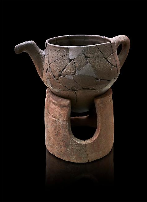 Hittite terra cotta teapot with strainer spout on a charcoa; burner base  . Hittite Period, 1600 - 1200 BC.  Hattusa Boğazkale. Çorum Archaeological Museum, Corum, Turkey. Against a black bacground.