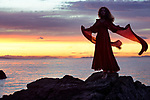 Artistic portrait of a young woman in long red dress flying in the wind dancing on the rocks of an ocean shore in sunset nature scenery Image © MaximImages, License at https://www.maximimages.com
