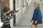 "Ireland The Troubles. Belfast young boy with top gun ""shooting"" his sister . Belfast. 1980s Playing with guns."