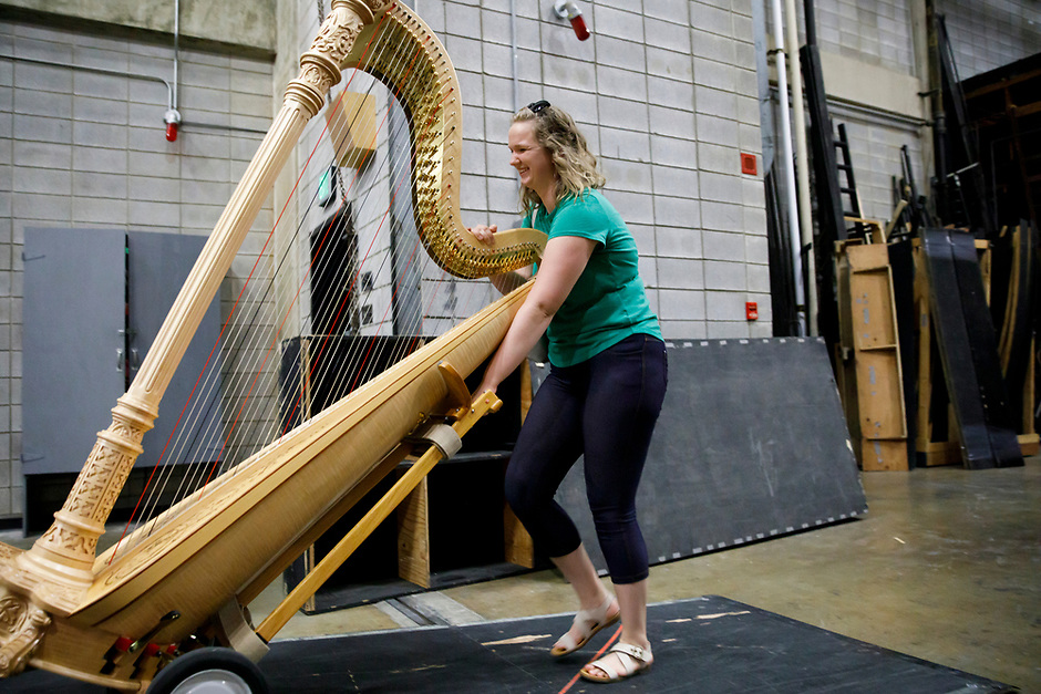 USA International Harp Competition Program Coordinator Melanie Mashner wheels a harp onto stage for an orchestra rehearsal for Final Stage at the 11th USA International Harp Competition at Indiana University in Bloomington, Indiana on Friday, July 12, 2019. (Photo by James Brosher)