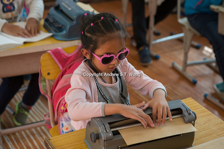 Blind Tibetan student Samten uses a braille writer during a lesson at the School for the Blind in Tibet, in the capital city of Lhasa, September 2016.