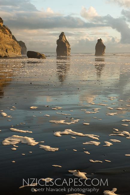 Sunset on coastline at Three Sisters rock formation and Tongaporutu River near Taranaki, New Plymouth, Taranaki Region, North Island, New Zealand, NZ