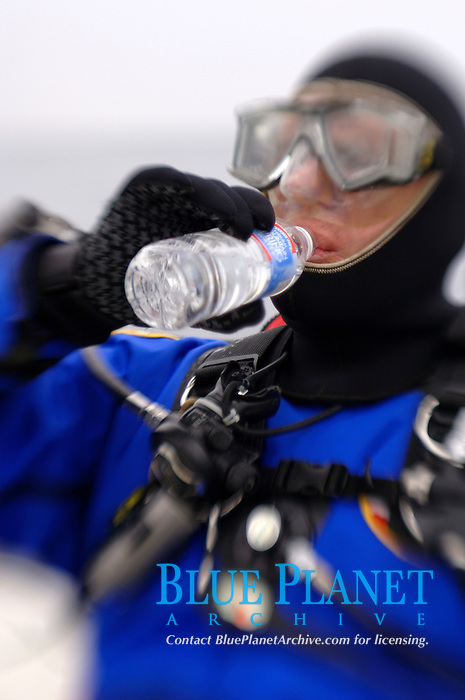 Scuba diver drinking water from bottle, select focus, MR