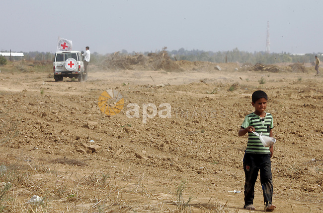 A Palestinian boy walks near an International Committee of the Red Cross (ICRC) vehicle as the comittee assists Palestinian farmers to repair their fields that were devastated during the Israeli army summer's military offensive on the Gaza Strip on October 22, 2014, in Khan Yunis' Khuzaa neighbourhood in the southern Gaza Strip near the Israeli border. Photo by Abed Rahim Khatib