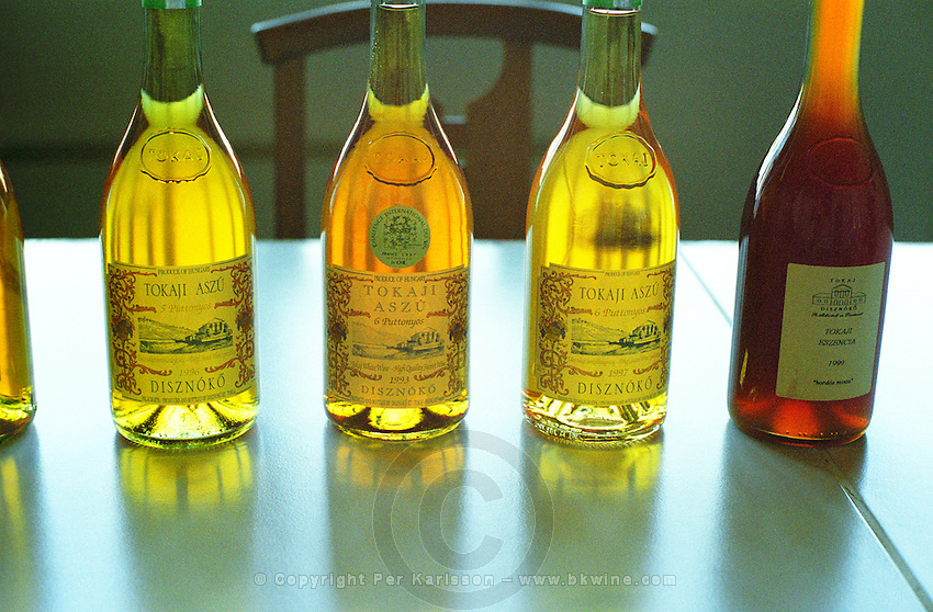 """Bottles of Tokaj wine at the Disznoko tasting room: Aszu 5 Puttonyos 1996, 6 Puttonyos 1993, 6 Puttonyos 1997, Eszencia 1999 """"hordos minta"""". There is a remarkable difference in colour. Generally the deeper the older. And the eszencia is even darker and not quite clear. The aszus are really much more of a wine experience. The Disznók? winery is owned by AXA Millesimes, a French insurance company. Disznoko means pig's head since a big rock in the vineyard supposedly looks like that. The new winery is impressive and a vast amount of money has been invested. Credit Per Karlsson BKWine.com"""
