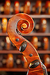 Neck of a Cello in profile with violins on shelves behind.  Music shop intrior.