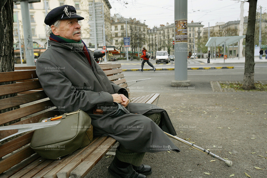"""Switzerland. Geneva. Poverty in Geneva. Henri Delaye is a swiss from the Geneva state and is 63 years old. He is homeless and sits on a bench in the """" Plaine de Plainpalais"""". His cap is covered with paper clips. Model Released. © 2005 Didier Ruef"""