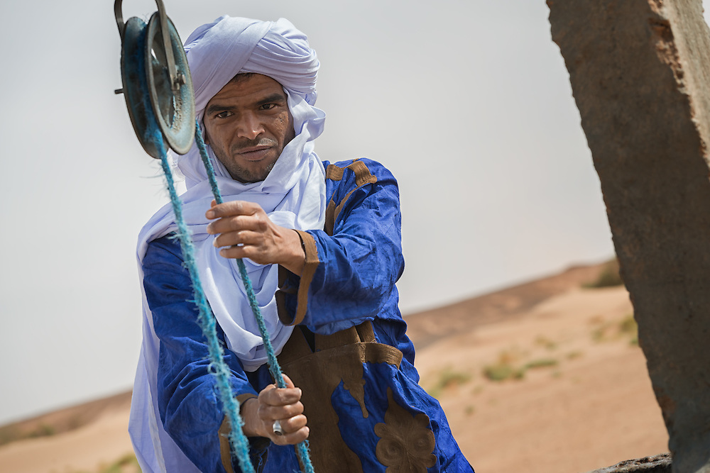 Moroccan man dressed in a traditional gandora at a well in the Sahara desert.   Rosa Frei - Photography