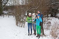 """Vogelbeobachtung im winterlichen Garten bei Schnee, Familie beim Vögel gucken, Fernglas, """"NABU Aktion Stunde der Wintervögel"""", family watching birds, bird watching in winter, garden, snow, binoculars"""