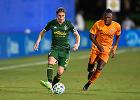 LAKE BUENA VISTA, FL - JULY 18: Jorge Villafaña #4 of the Portland Timbers passes the ball while pressured by Alberth Elis #7 of the Houston Dynamo during a game between Houston Dynamo and Portland Timbers at ESPN Wide World of Sports on July 18, 2020 in Lake Buena Vista, Florida.