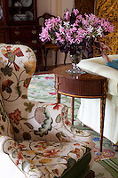 Detail of the Jacobean style floral pattern on a wing-backed chair in the drawing room