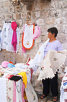 Women selling embroideries, hats, table cloths and other decoration, to tourists while sitting embroidering or stitching in the Marina harbour Dubrovnik, old city. Dalmatian Coast, Croatia, Europe.
