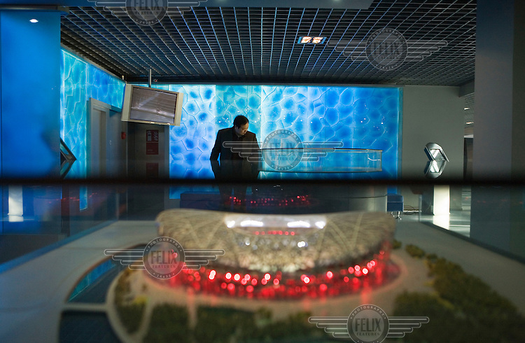 A man looks at the exhibits in the Beijing Planning Exhibition Hall. Plans for all the 2008 Olympic Games and models of the various stadiums, including the National Stadium, are on show here.