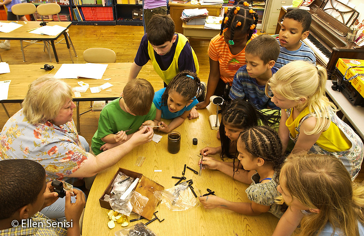 MR / Schenectady,NY.Yates Arts-in-Education Magnet School, urban public school, Grade 3.Boy (8) uses Discovery Scope (a small, hand-held micro-macro viewing tool) to observe magnified salt crystals and then draws what he sees in his  microscope experiment journal..MR: Pec2.©Ellen B. Senisi