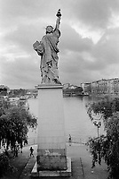 """France. Ile-de-france Department. Paris. Original Statue of Liberty on the Île aux Cygnes near the Grenelle Bridge. Given to the city  and inaugurated on July 4, 1889, it looks southwest, downriver along the Seine. Its tablet bears two dates: """"IV JUILLET 1776"""" (July 4, 1776: the United States Declaration of Independence) like the New York statue, and """"XIV JUILLET 1789"""" (July 14, 1789: the storming of the Bastille). Men jogging.  10.06.10 © 2010 Didier Ruef"""